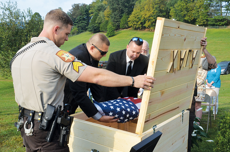Members of the Cherokee County Sheriff's Office place the remains of Deputy K-9 Ajax into a coffin that was buried at the law enforcement training center in Marble. Photos by Penny Ray