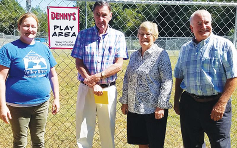 "Animal shelter manager Kirsty Waller and Valley River Humane Society President Jeff Manson reveal the sign reading ""Denny's Play Area"" to its namesake, Denny Kendall, and his wife, Diane."