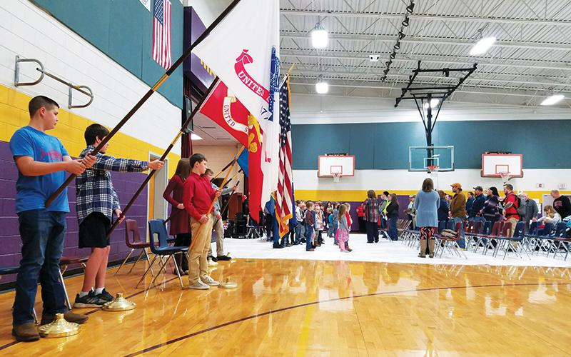 Colton Berrong, Samuel Henry, Isaiah Matheson, Molly Ledford, Gabriella Ermosos and Levi Chastain present the flags as veterans and their families enter the Martins Creek School gym Tuesday morning.