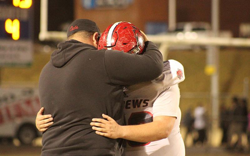 Mary White/Contributing Photographer: Senior Brawley Stillwell and Andrews head coach James Phillips share a moment following the Wildcats' second-round loss to the second-seeded Elkin Elks.
