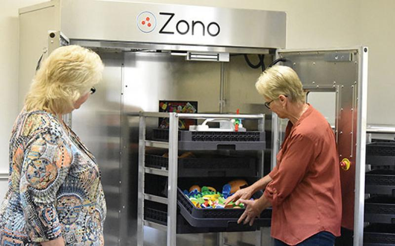 Health specialist Joyce Young and Head Start center director Sharon Palmer show how the Zono Cabinet works at Hilltop Head Start in Andrews. Photo by Samantha Sinclair