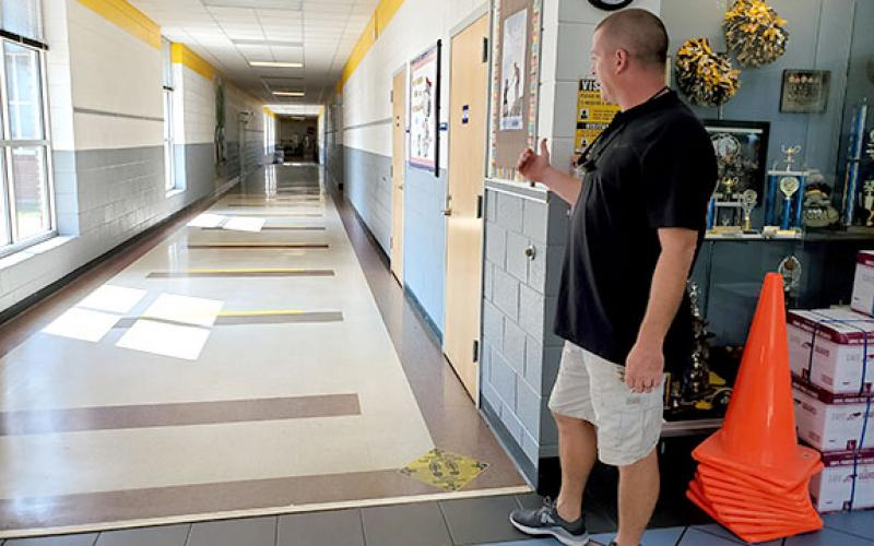 Murphy Elementary School Principal Dane Rickett shows decals placed on the floors to remind children to maintain 6 feet of distance. Children were told to not walk in the center of the hallway within the yellow stripes. Photo by Samantha Sinclair