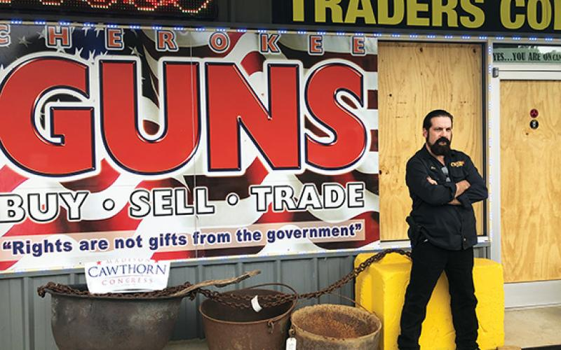 "Penny Ray/pennyray@cherokeescout.com ""Doc"" Wacholz stands outside Cherokee Guns on U.S. 64 West, which was burglarized on Sept. 13. The store's window and door were boarded up until the glass could be replaced."