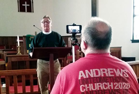 Jeanne Powell/For the Cherokee Scout Robby Morris records the Rev. Tom Jolly as he preaches his sermon in the sanctuary of Andrews United Methodist Church.