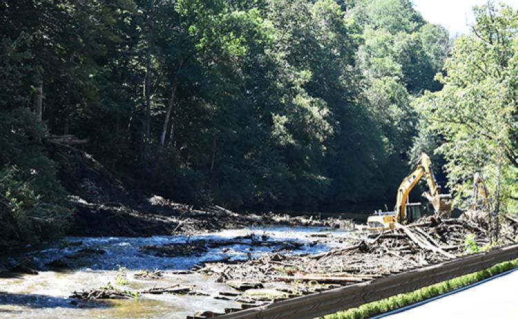 Contractors using heavy equipment work to remove debris from the Nantahala River.