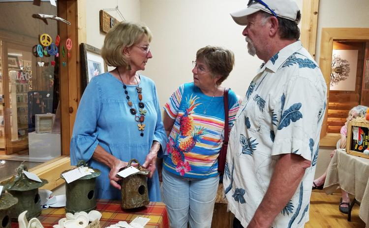 At the Fall into Art festival Friday during the Art Walk, Cathy Mozley tells Debbie and Jerry Cromer of Edisto Beach, S.C., about her ceramic bird houses.