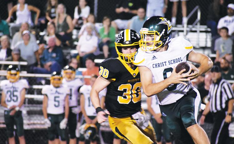 Murphy's Chandler Wood chases Christ School quarterback Navy Shuler on Friday.