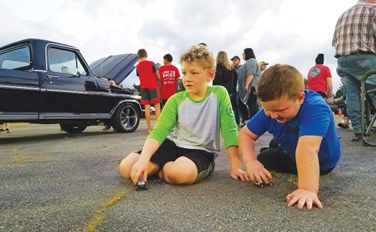 With the Mayor's Choice-winning truck behind them, Braylen Guffie, 8, and Kip Beaver, 5, play with toy cars Saturday during Andrews Cruise Night for the Kids.