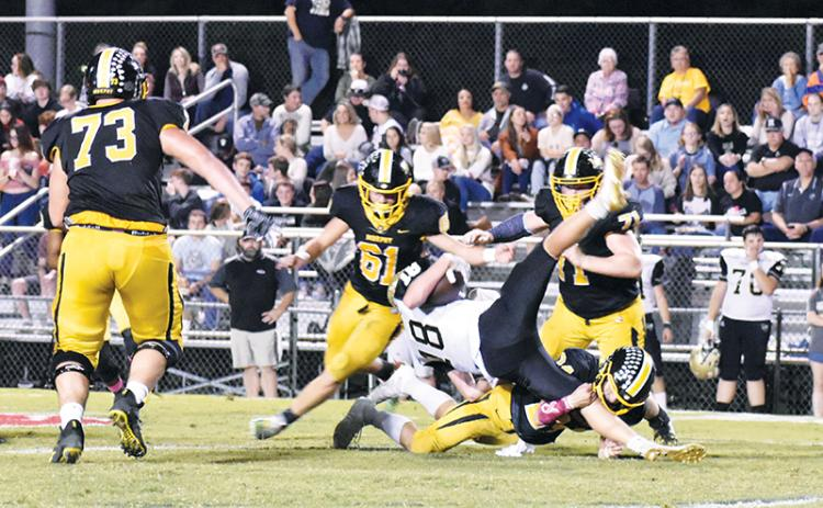 Murphy defenders swarm as linebacker Ray Rathburn upends a Hayesville runner during the Bulldogs' 62-14 shellacking of the Yellow Jackets on Friday night.