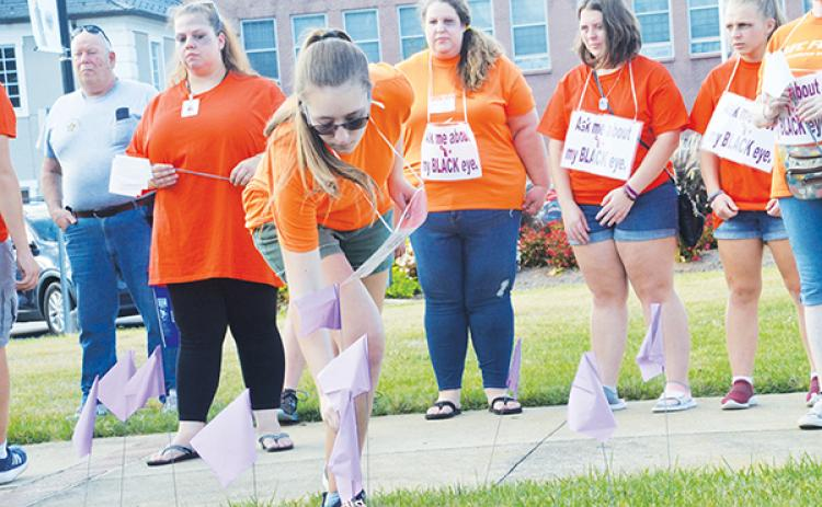 Jasmine Weaver plants a flag in remembrance of victims who died as a result of domestic violence. In rear wearing orange are Jessica Vernon, Stacy Van Buskirk, Lilli Johnson and Allana Johnson (from left).