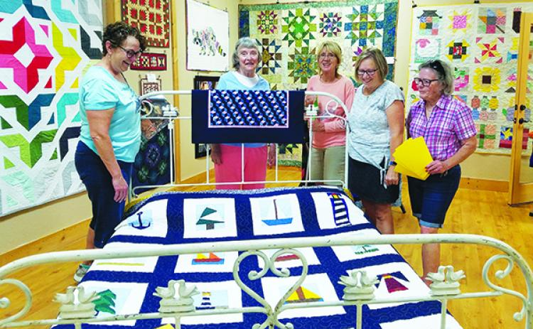 "Janelle Warren, Maureen Ripper, Cynthia Gonzalez, Gayle Cowdin and Joanna Marren put the finishing touches on the ""Quilts!"" exhibit at the Murphy Art Center downtown."