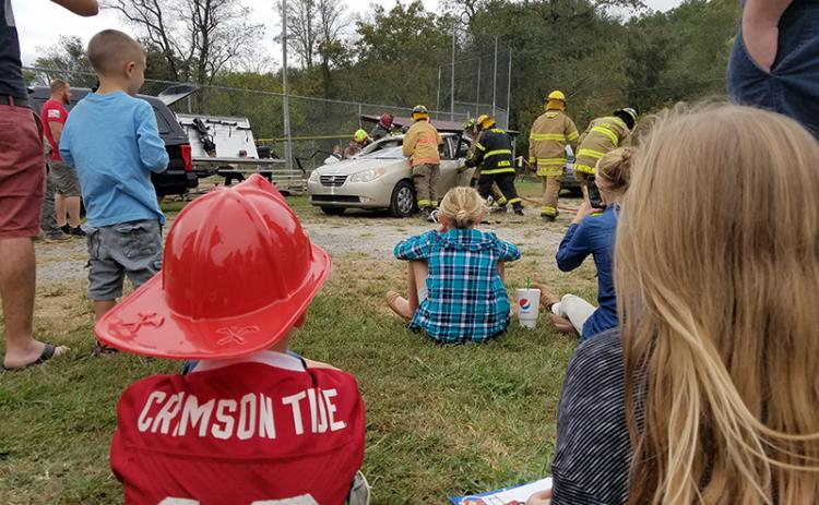 "Children watch as teams of volunteer firefighters practice extraction skills and show the difference in tools during the Car Extraction Race at the Ranger Volunteer Fire Department on Saturday. ""They're ripping the doors off?"" one child exclaimed as the volunteers carefully removed pieces of the car."