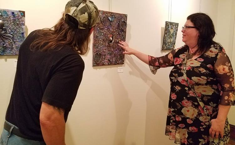 "Marie Gunther points out shotgun shells used in her three dimensional piece ""Through a Glass Darkly"" to Tom Vogler. The piece was on display at the Andrews Art Museum on the second floor of the Valleytown Cultural Arts Center during Writers & Wine."