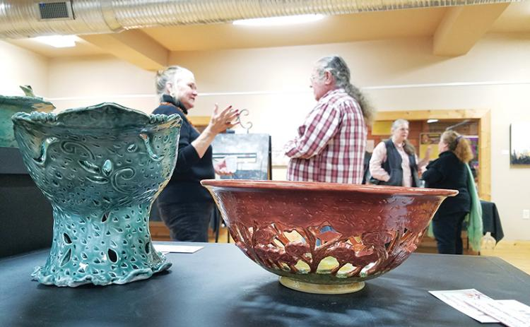 "The ""Fashioned in the Clay"" show displays a variety of items, from practical to decorative, including Lisa Proper's intricate fruit and centerpiece bowls. In the background, Elo-ly Bailey, David Vowell, Kathy Ross and Proper hold conversations during the exhibit's opening."