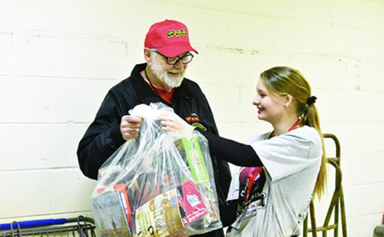 While volunteering at the Toys for Tots distribution, John Evans of Bellview is handed a bag of toys for a family by Jade Stiles. Photo by Samantha Sinclair