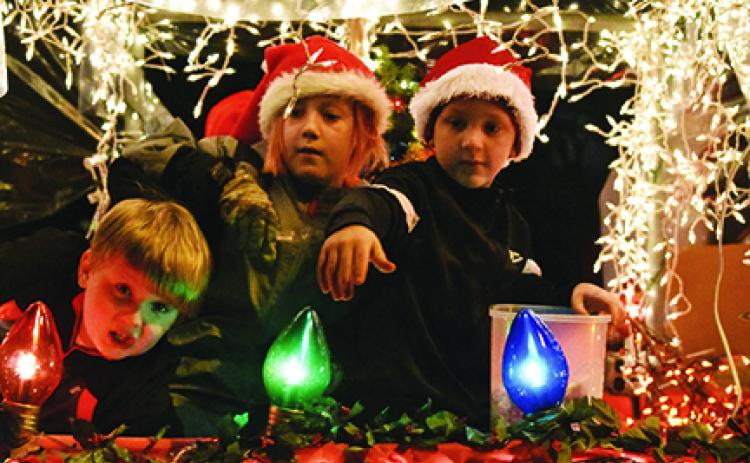 In their snow globe float, Cub Scouts Bradyn Thompson, Zack Bryant and Cale Wilson (from left) look for friends to throw candy to along the parade route Saturday night. Photo by Samantha Sinclair