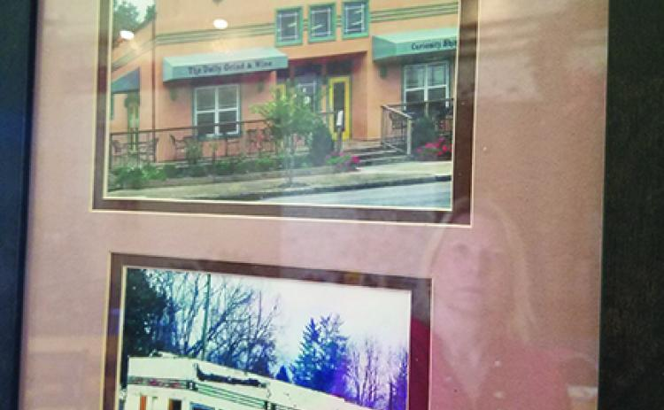 On the wall at FernCrest Winery in Andrews, Jan Olson (reflected) has framed photos that show the building's past. Photo by Samantha Sinclair