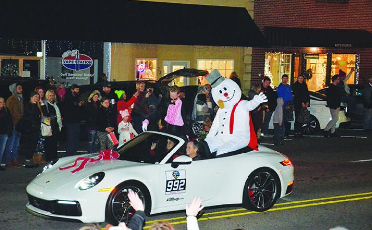Frosty the Snowman waves to the crowd pf parade watchers as he's escorted down Valley River Avenue during A Very Murphy Christmas on Saturday evening. Photo by Penny Ray