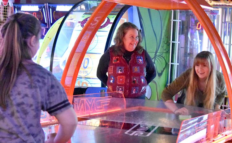During the Big Brothers Big Sisters Christmas Party at the UltraStar Multi-tainment Center in December, Sallie Sompayrac watches Emily Barnes plays air hockey with her Little. Photo by Samantha Sinclair