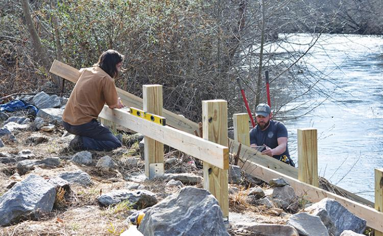 Jeremiah Smith of Big Deck Decking helps Nick Oliver of the Hinton Rural Life Center find the right angle for the kayak ramp they are building just below the bridge on Bulldog Drive in Murphy. Photo by Samantha Sinclair