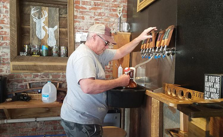 Terry Vaughn fills a growler with Bimbo blond ale for a customer at Snowbird Mountains Brewery in Andrews on Saturday. Photo by Samantha Sinclair