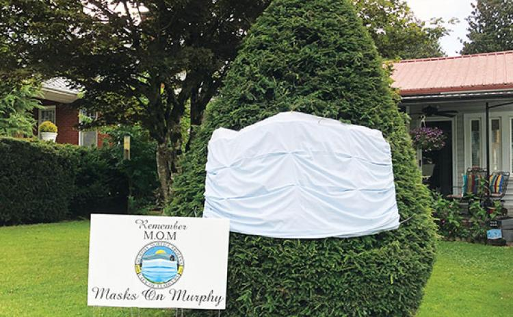 Murphy Councilwoman Gail Walker Stansell created this sign and decorated a tree outside her house to encourage people to wear masks and help slow the spread of COVID-19.