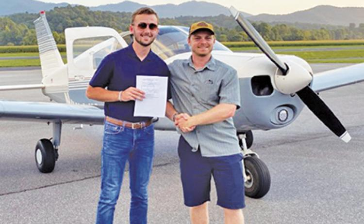 After getting his license, Seth Fullerton is congratulated by Grady Flynn, one of the instructors at the airport.
