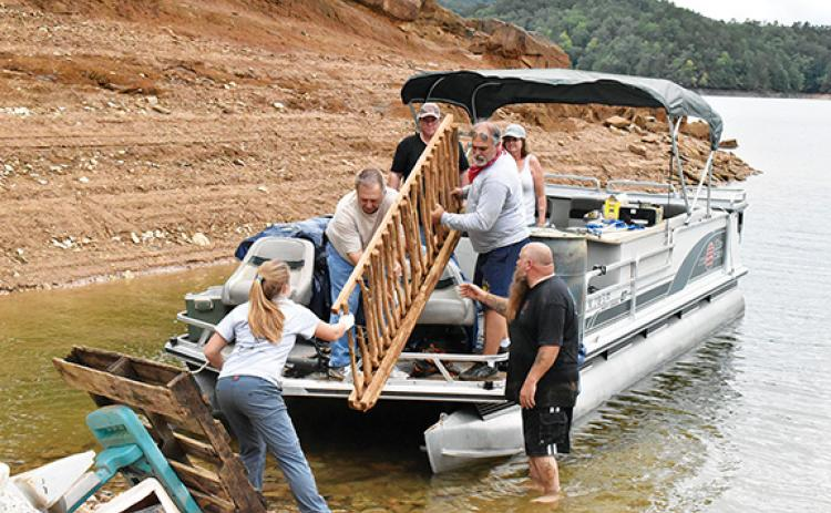 Noah Shatzer/sports@cherokeescout.com Mainspring Conservation Trust outreach associate Rachel Newcomb helps a pontoon boat of retired firefighters unload the trash they picked up around Hiwassee Lake.