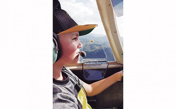 Timothy Raxter flies a plane for the first time with assistance from airport manager Garland Trull. The Western Carolina Youth Aviation Foundation is hoping to give more kids the same opportunity Raxter had.