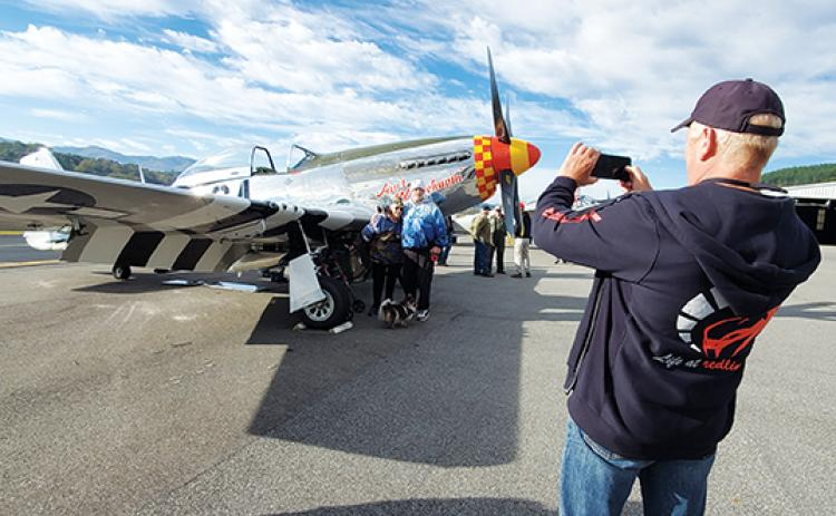 U.S. Air Force veteran Carol Kingsley poses with her son, John, in front of an AT-11 plane as Gary Carter takes their photo. Kingsley is a Korean War veteran who joined when the Air Force started to welcome women. Photo by Samantha Sinclair
