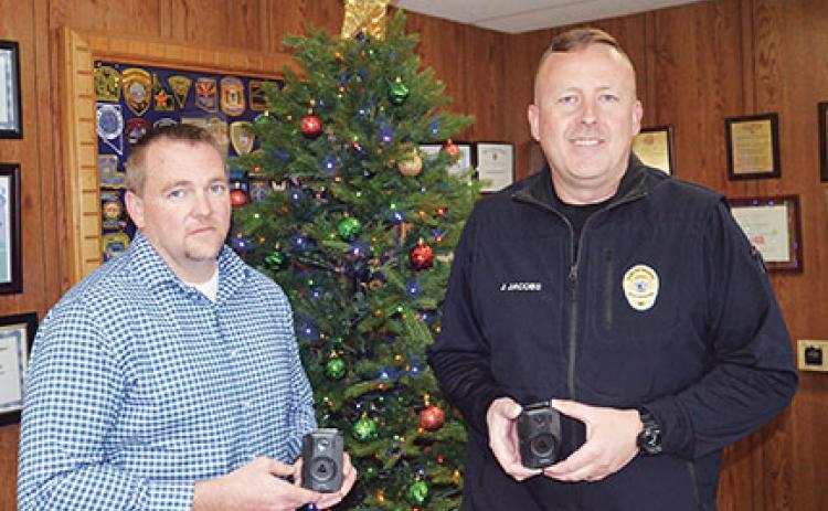 Penny Ray/pennyray@cherokeescout.com Murphy assistant police chief Dustin Smith and Police Chief Justin Jacobs demonstrate the department's new body cameras.