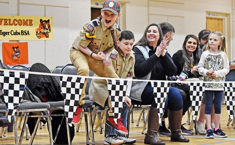 Ethan Reeves jumps for joy as his car comes in first place during the Nantahala District of Cub Scouts' Pinewood Derby on March 1.