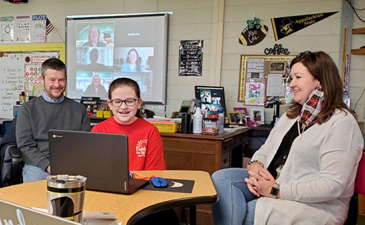 Samantha Sinclair/scoutingaround@cherokeescout.com Abby Lee, with parents Tim and Jackie beside her, listens as College Foundation of North Carolina regional representative Devon McCarthy-James congratulates her during videoconference presentation Feb. 10. On the screen in the background are McCarthy-James, Hiwassee Dam Elementary/Middle School counselor Lauren Grubb, teacher Whitney Tanner and Principal Ruby Cutshaw.
